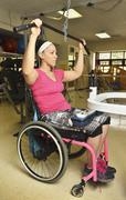 Paraplegic woman in wheelchair working out in physical therapy Stock Photos