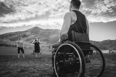 Paraplegic athlete in wheelchair playing on field Stock Photos