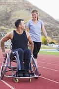 Paraplegic athlete in wheelchair with girlfriend on track - stock photo