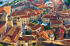 Stock Photo of View of old town on sunset. Red tiled roofs in Kotor
