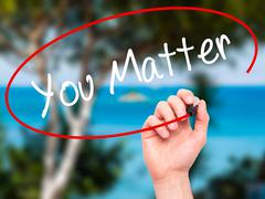 Man Hand writing You Matter with black marker on visual screen. Stock Photos