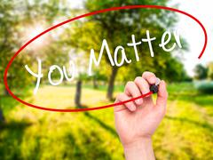 Man Hand writing You Matter with black marker on visual screen. - stock photo
