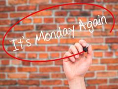 Man Hand writing It's Monday Again with black marker on visual screen. - stock photo