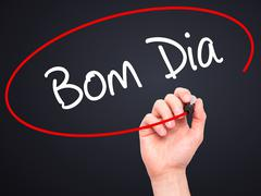 "Man Hand writing ""Bom Dia"" (In portuguese - Good Morning) with marker Stock Photos"