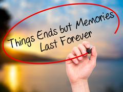 Man Hand writing Things Ends but Memories Last Forever with marker - stock photo