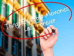 Man Hand writing Things Ends but Memories Last Forever with marker Stock Photos