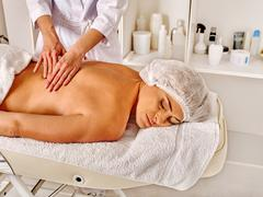 Woman middle-aged in spa salon with beautician - stock photo
