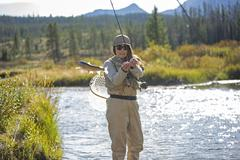 Caucasian woman fishing in rural river Stock Photos