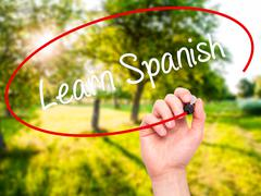 Stock Photo of Man Hand writing Learn Spanish with black marker on visual screen