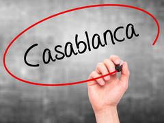 Stock Photo of Man Hand writing Casablanca with black marker on visual screen.