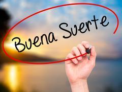 Man Hand writing Buena Suerte( Good Luck in Spanish) with marker - stock photo