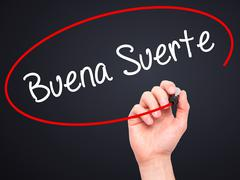 Man Hand writing Buena Suerte( Good Luck in Spanish) with marker Stock Photos