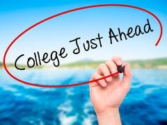 Man Hand writing College Just Ahead with black marker on visual screen. - stock photo