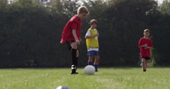 Kids training with a soccer ball on a field. Shot in slow motion on RED Epic. - stock footage