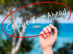 Man Hand writing College Just Ahead with black marker on visual screen. Stock Photos