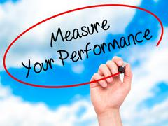 Stock Photo of Man Hand writing Measure Your Performance with black marker on visual screen.