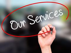 Man Hand writing Our Services with black marker on visual screen - stock photo