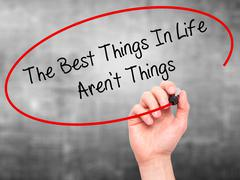 Man Hand writing The Best Things In Life Aren't Things with marker - stock photo