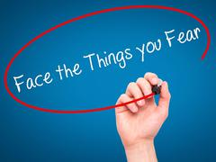 Man Hand writing Face the Things you Fear with black marker on visual screen. - stock photo