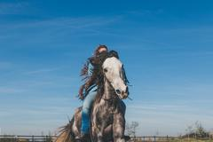 Pretty girl riding her grey horse - stock photo