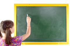 Stock Photo of First grade pupil a girl writing on green blackboard
