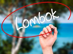 Man Hand writing Lombok with black marker on visual screen. Stock Photos