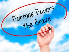 Man Hand writing Fortune Favors the Brave with black marker on visual screen. - stock illustration