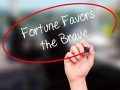 Stock Illustration of Man Hand writing Fortune Favors the Brave with black marker on visual screen.