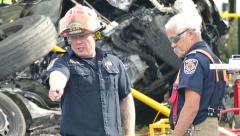 Two Firefighters talking on the scen of a crash of an 18-wheeler Stock Footage