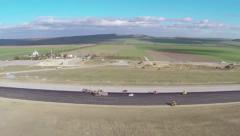 Tracked paver laying fresh asphalt pavement on an airport runway, aerial view Stock Footage