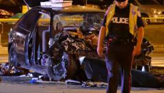 Police officers standing in front of wrecked car Stock Footage