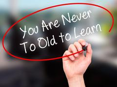 Man Hand writing You Are Never Too Old to Learn with marker on visual screen. - stock illustration