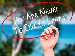 Man Hand writing You Are Never Too Old to Learn with marker on visual screen. Stock Illustration