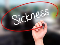 Stock Illustration of Man Hand writing Sickness with black marker on visual screen.
