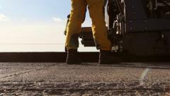 Tracked paver laying fresh asphalt pavement Stock Footage