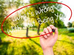 Man Hand writing What's Wrong With Just Being You? with marker on visual screen. - stock illustration