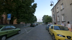 Walking and riding bikes on Koscielna street, next to St. Mary's Church, Warsaw Stock Footage
