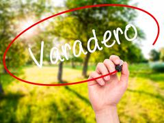 Man Hand writing Varadero with black marker on visual screen. - stock illustration