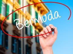 Stock Illustration of Man Hand writing Bermuda with black marker on visual screen