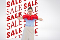 Stock Photo of Composite image of tough businesswoman posing with red boxing gloves