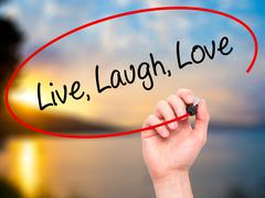 Man Hand writing Live Laugh Love with black marker on visual screen. - stock illustration
