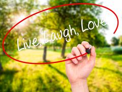 Man Hand writing Live Laugh Love with black marker on visual screen. Stock Illustration