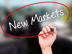 Stock Illustration of Man Hand writing New Markets with black marker on visual screen.