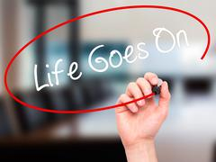 Man Hand writing Life Goes On with black marker on visual screen. Stock Illustration