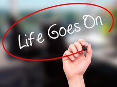 Man Hand writing Life Goes On with black marker on visual screen. - stock illustration