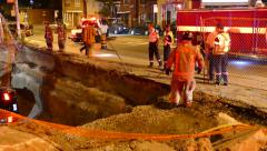 Firefighters on scene of car into a pit Stock Footage