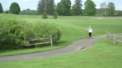 Walking and biking on a path in the park Stock Footage