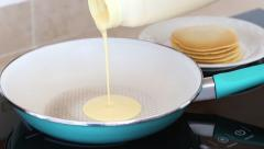 Pouring pancake mixture on a frying pan Stock Footage