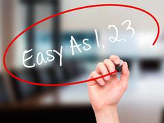 Stock Illustration of Man Hand writing Easy As 1,2,3... with black marker on visual screen.