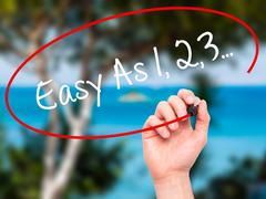 Man Hand writing Easy As 1,2,3... with black marker on visual screen. Stock Illustration